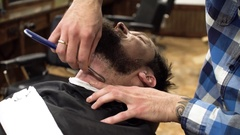 Man having shave at barber shop close up. Professional barber using straight Stock Footage