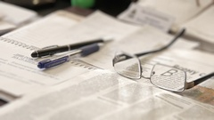 Glasses on a newspaper with a pen Stock Footage