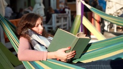 Relaxed girl wearing scarf because of coolness and reading book on hammock Stock Footage