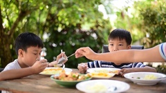 Thai boy eating with food on the wooden table with his family Stock Footage