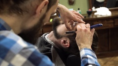Professional barber shave client's beard with straight razor. very concentrated Stock Footage