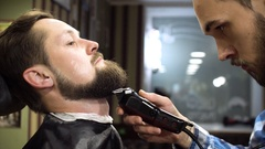 Hairstyling process. Close-up of a barber drying hair of a young bearded man Stock Footage