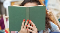 Girl hiding behind book and being flirtatious while smiling to the camera Stock Footage