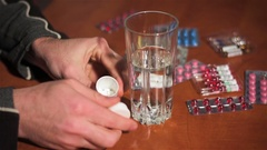 Man pulls white pill out of container and drinks it with water Stock Footage