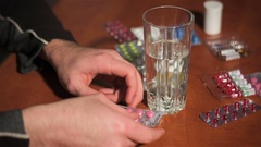 Man pulls pink pill out of silver blister and drinks it with water Stock Footage