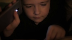 Boy reading book before going to sleep under covers Stock Footage