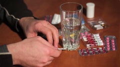 Man pulls white pill out of silver blister and drinks it with water Stock Footage