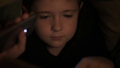 Six year old boy read book under covers at night and illuminates flashlight Stock Footage