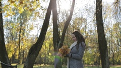 Excited young woman having fun throwing yellow leaves in the sunny fall park. Stock Footage