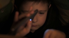 Six year old boy read book under covers at night Stock Footage