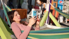 Relaxed girl lying in hammock and browsing internet on smartphone Stock Footage