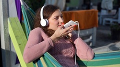 Girl wearing headphones and using loudspeaker while talking on cellphone Stock Footage