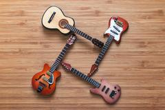 Set of four guitars on a wooden background. Kuvituskuvat