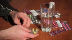 Man pulls yellow pill out of silver blister and drinks it with water Stock Footage