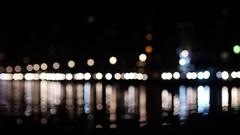 Night traffic in Thessaloniki Greece - running car lights reflected sea bay Stock Footage