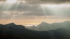 Sun rays through the clouds floating over the mountains and the sea. Timelaps Stock Footage