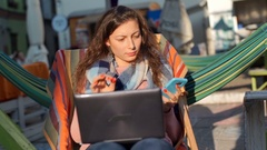 Girl compares information on smartphone and laptop while sitting outside Stock Footage