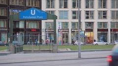 Cars drive next to Potsdamer Platz Ubahn underground subway station, Berlin Stock Footage