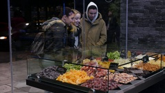 Young people watch a shop showcases layout of dried citrus sweets - Thessaloniki Stock Footage