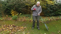 Elderly Man Rakes His Garden 4K Stock Footage