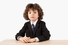 Curled small boss sitting at the table and looking into the camera Stock Photos