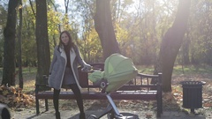 Young mother walking with a baby pram (stroller, carriage) in the park in autumn Stock Footage