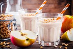 Healthy breakfast: smoothie with granola, red apple and milk Stock Photos