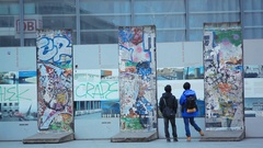Tourists read info at Berlin Wall remains, Potsdamer Platz, Berlin, Germany Stock Footage