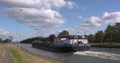 Inland cargo ship on inland waterway  canal sails off camera Stock Footage