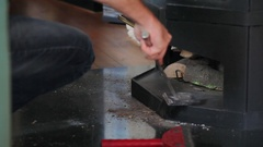 Man cleans dust next to wood burning oven heating stove Stock Footage