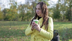 Beautiful brunette girl in yellow coat holding a cup of coffee in the park. Stock Footage
