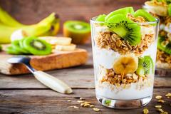 Healthy breakfast: yogurt parfait with granola, banana and kiwi Stock Photos