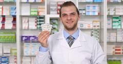 Happy Pharmacist Man Showing Pills Looking Camera Hand Gesture Ok Sign Left Pan Stock Footage