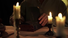 Vintage 1800s man reading bible by candlelight 4k Stock Footage