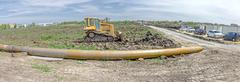 Panoramic view on landscape with bulldozer and long tool Stock Photos