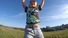 Father lifts his little son in a meadow on a sunny day. Dad playing with baby Arkistovideo