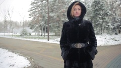 Young beautiful woman in stylish mink coat on a background of a winter park Stock Footage