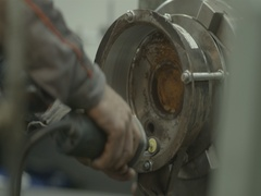 Worker in a factory processed metal detail with power tool in slow motion Stock Footage