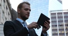 Confident Businessman Using Digital Tablet Buying Online Credit Card UK Building Stock Footage