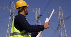 Experienced Engineer Man Reading Blueprint in Industrial Area Wire Lines Network Stock Footage
