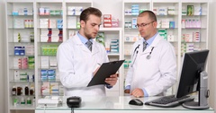 Two Pharmacists Men Talking and Writing Clipboard List of Drugs Pharmacy Shop Stock Footage