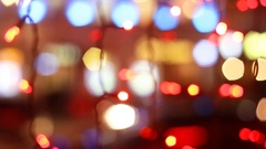 Colorful holiday bokeh night city. Blurred silhouettes of cars and people Stock Footage