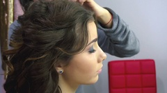 Beautiful woman having her hair curled in barber salon Stock Footage