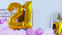 MED young attractive Caucasian female holding air balloons shaped as number 21 Stock Footage