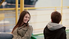 A young brunette and young man are sitting next to each other on a bench and Stock Footage