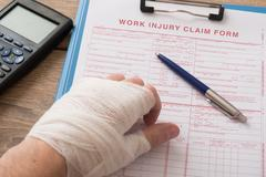 Worker injured hand filling a insurance claim form Stock Photos