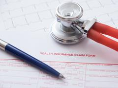 Health insurance claim form with pen and stethoscope Stock Photos