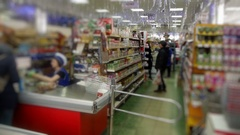 Customers make purchases at the supermarket and the cashier sits in the Stock Footage
