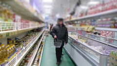 Elderly man goes into the supermarket with an empty shopping cart Stock Footage