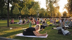 Yoga woman on green grass.. big group of adults attending a yoga class outside Stock Footage
